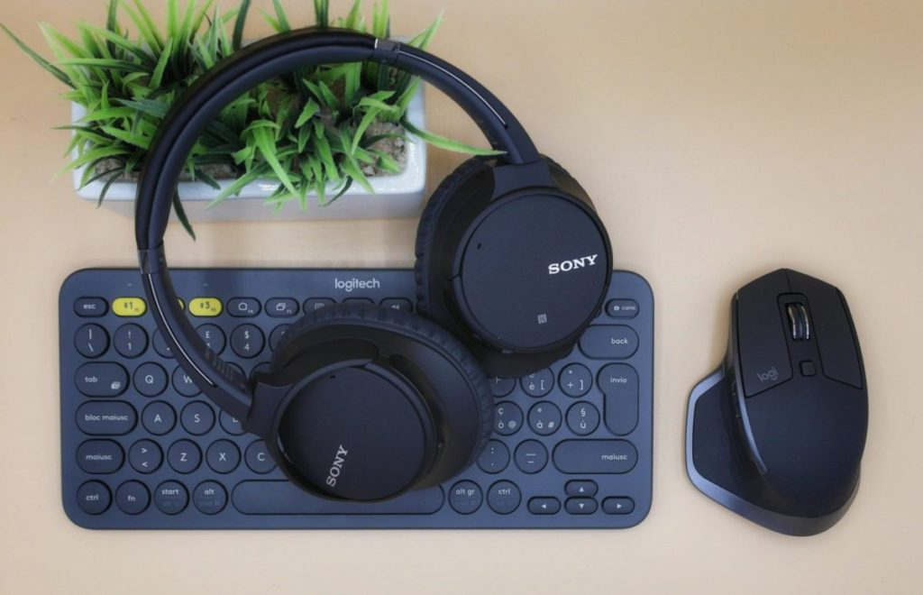 black Sony wireless headphones on black computer keyboard